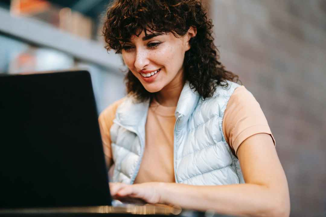 crop smiling freelancer working on laptop at cafe table outdoors
