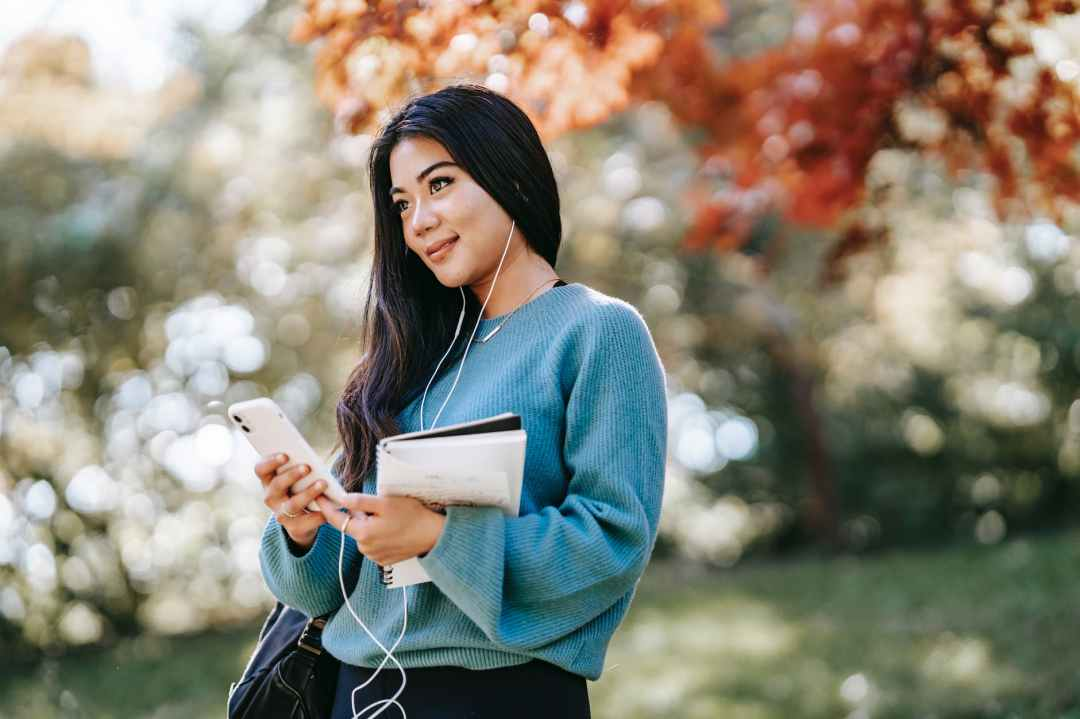 young woman enjoying music using smartphone in garden